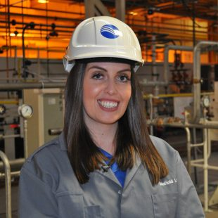 Jade White, wearing a hard hat and overall with the Sellafield Ltd logo on it.