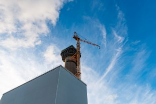 Colour image of the Windscale Chimney Pile 1 with a tower crane