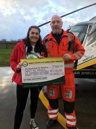 Sophie kelly presenting a cheque to the North West Air Ambulance.