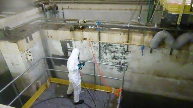 Man in protective suite jet-washing pond wall