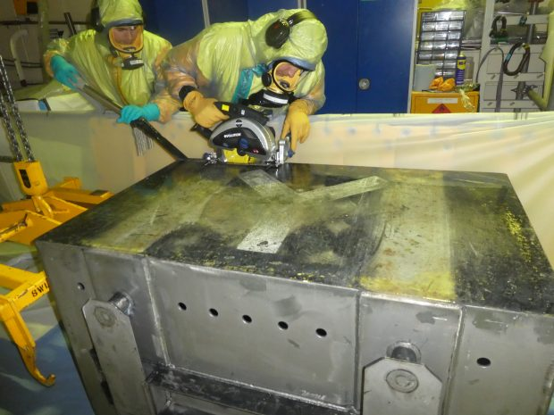Two men in protective suits cutting up skip