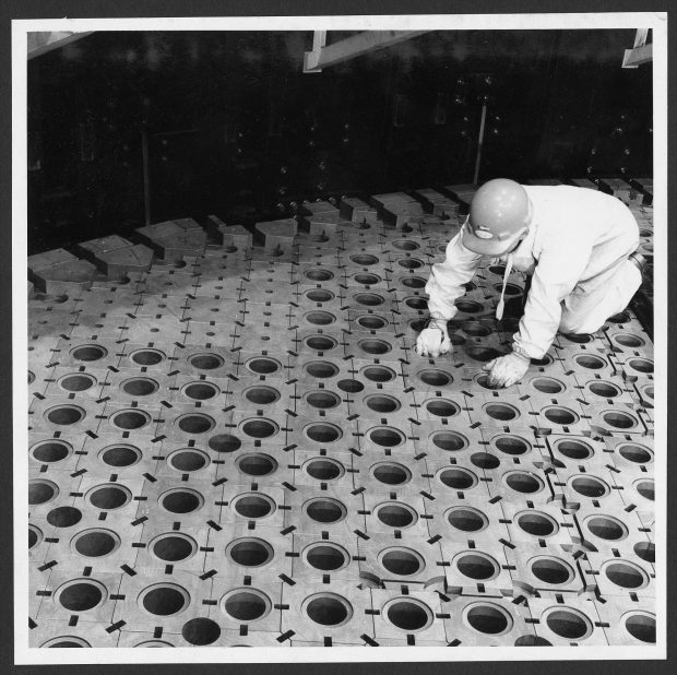 Black and white photo showing man kneeling on graphite blocks