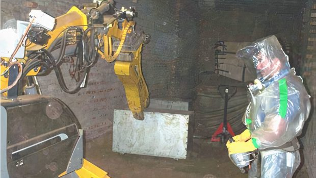 Sellafield worker in protective suit next to robot cutting up waste
